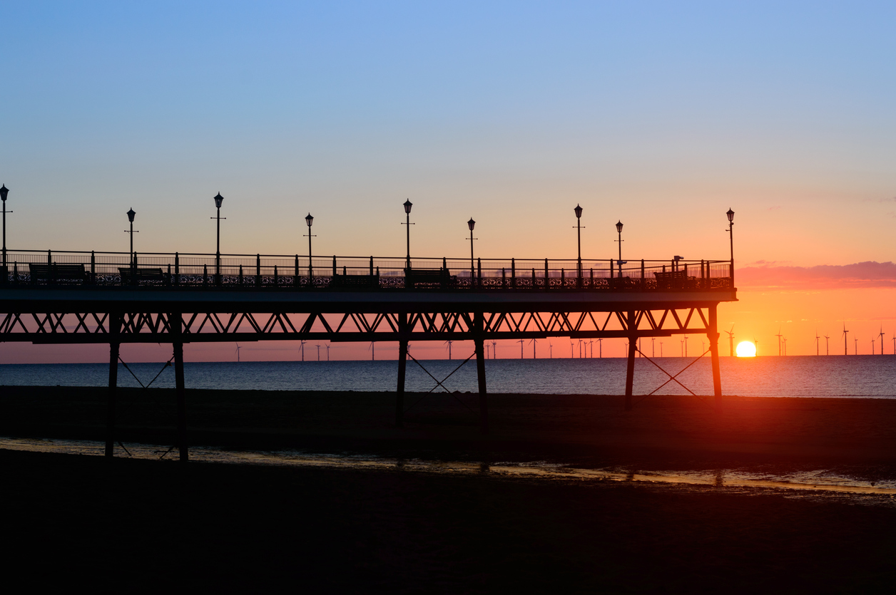 Skegness, England - June 8, 2015: The end of Skegness pier, at sunrise, in June. Wind farm can be seen in the distance. In Skegness, Lincolnshire, England.