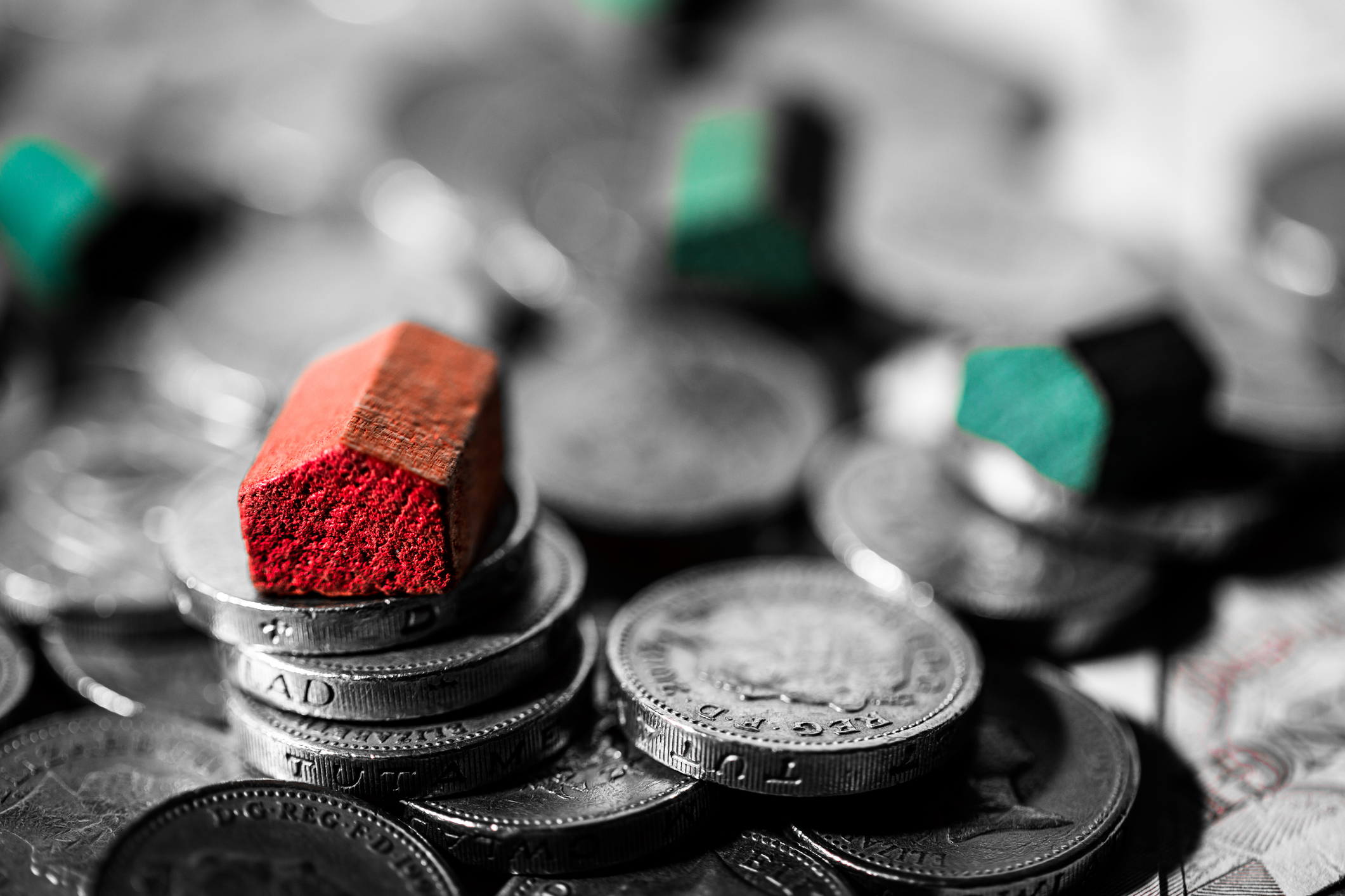 Macro close up image of red and green wooden houses on top of piles of golden British pound coins, illustrating a mortgage, housing and savings concept. All the colour has been desaturated apart from the red and green houses, leaving a mainly monochomr image. Horizontal image with extremely shallow depth of focus and lots of room for copy space.