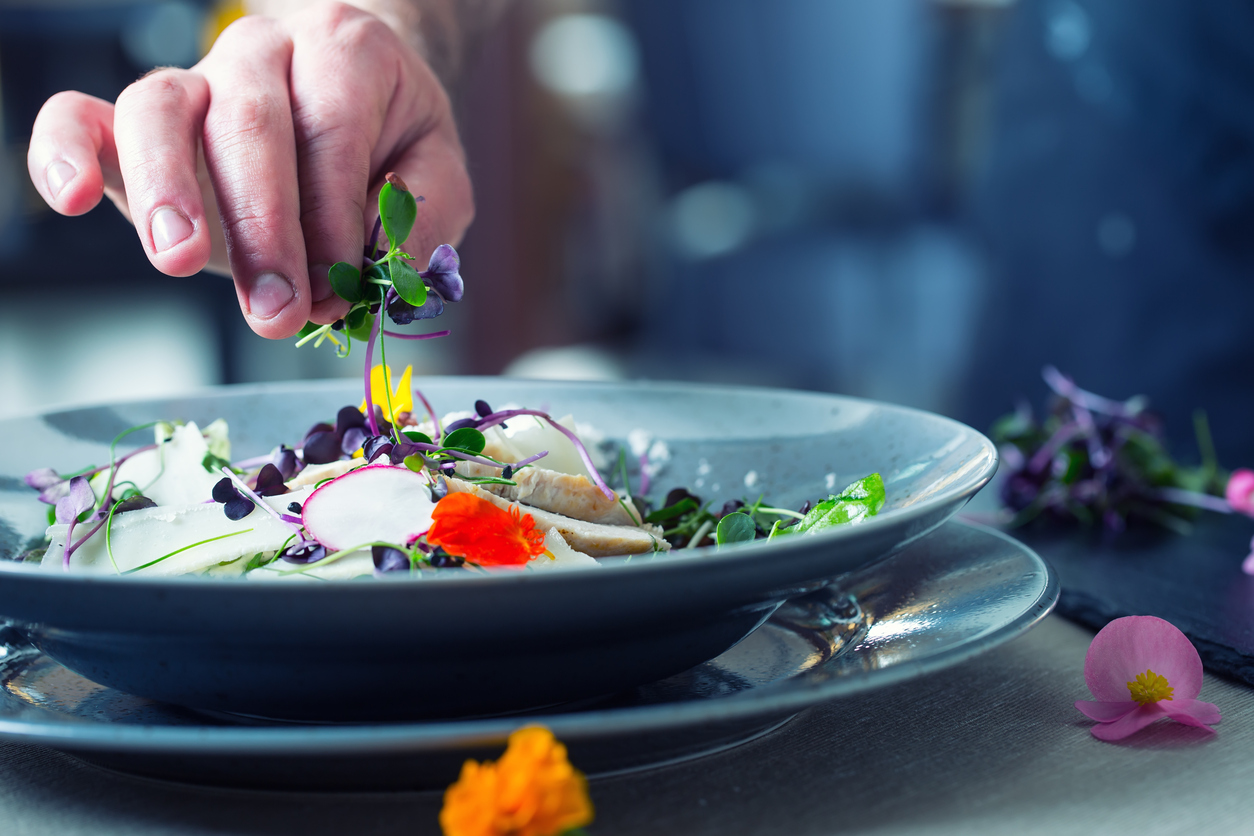 Chef in hotel or restaurant kitchen cooking, only hands. He is working on the micro herb decoration. Preparing vegetable salad with pieces of grilled chicken  meat - virgin sirloin.