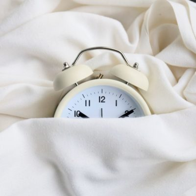 World Sleep Day, alarm clock under covers